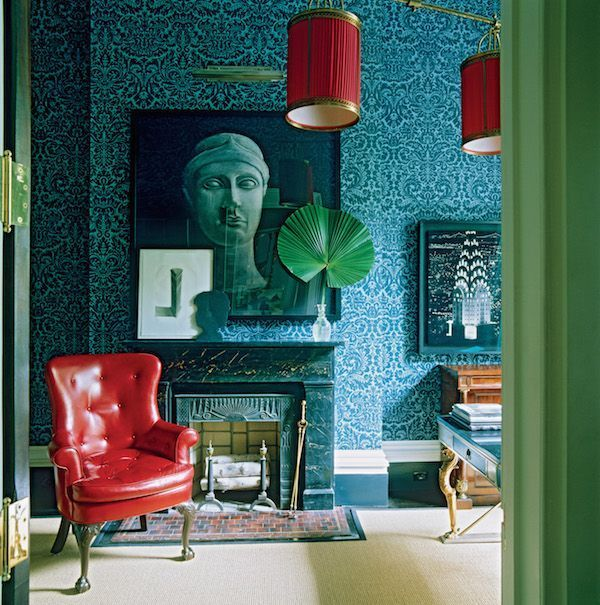 In the study a cherry-red leather armchair and lampshades create rich notes of contrast with the turquoise wallpaper in an ornate floral design